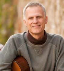 Close-up on Peter Mayer cradling guitar
