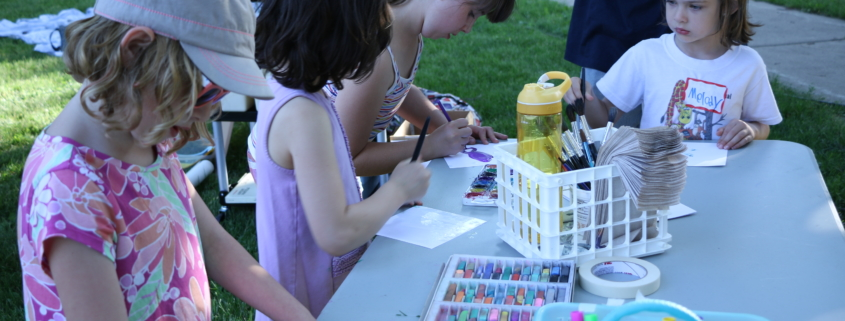 Four children doing mixed media art at a table outside