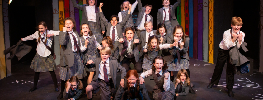 "Twenty middle school and high school actors dressed as school children singing the song ""Revolting Children"" from Matilda, the Musical onstage."